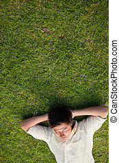 Elevated view of a man lying in grass with his eyes closed and his hands resting underneath his head