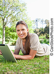 Smiling woman lying on the grass with her tablet computer
