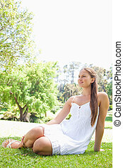 Woman relaxing on the grass in the park