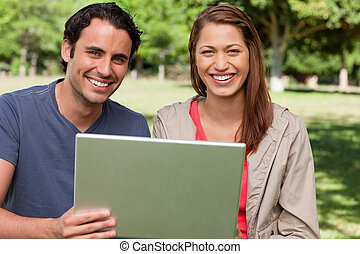 Two smiling friends looking ahead as they hold a tablet -...