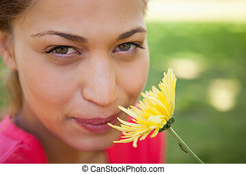 Woman looking upwards while smelling a yellow flower with...
