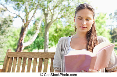 Woman sitting on a park bench while reading a book - Young...