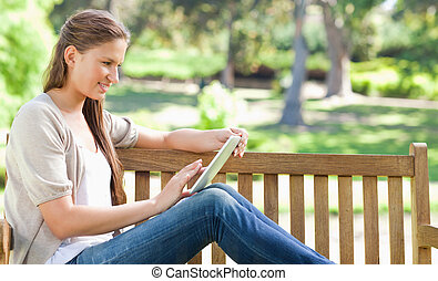 Side view of a woman using a tablet computer on a park bench...