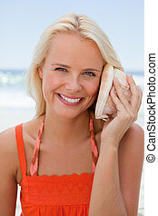 Woman holding a shell to hear the sound of the sea while showing a great smile