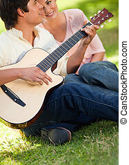 Man playing the guitar while his friend is listening to him