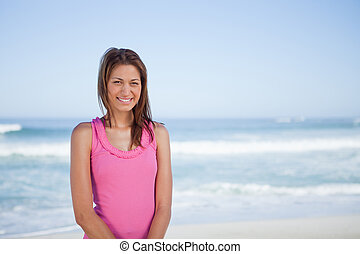 Young smiling woman standing upright in front of the sea