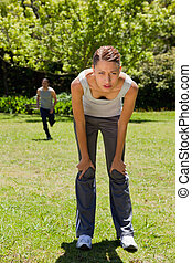 woman bending over while a man is running in the background...