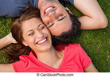 Two friends smiling with their eyes closed while lying head...