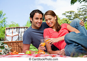 Two smiling friends looking directly in front of them while they hold glasses as they lie on a blanket with a view of the sky in the background