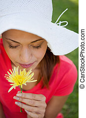 Woman wearing a white hat while smelling a yellow flower...