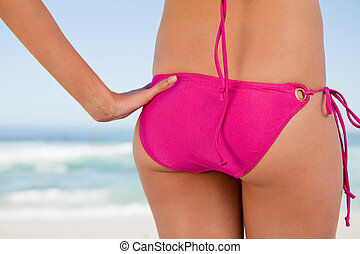 Rear view of a young woman body in pink swimsuit