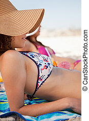 Young attractive woman sunbathing while lying on a beach towel