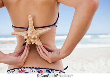 Rear view of a young woman holding a starfish on her back