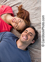 Close-up of two smiling friends lying next to each other as they look into the sky while on a grey quilt