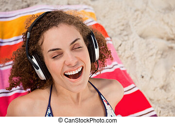 Young woman closing her eyes while listening to music