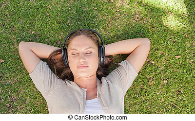Relaxed woman listening to music while lying on the lawn
