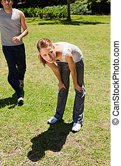 Woman bending over while a man is jogging behind her - Woman...