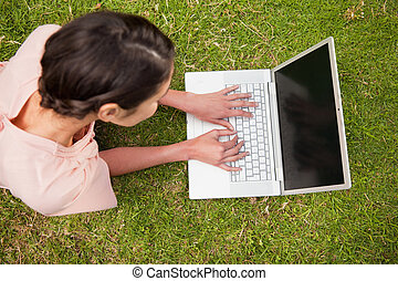 Elevated view of a woman using a laptop while lying down -...