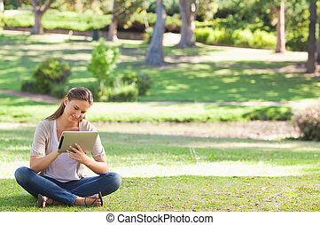Woman in the park with a tablet computer