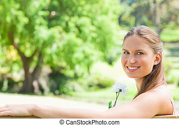 Side view of a smiling woman with a flower