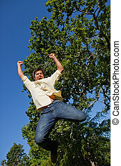 Man jumping off the ground while raising both of his arms...
