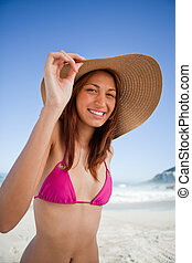 Smiling teenager wearing a pink swimsuit while holding her hat brim
