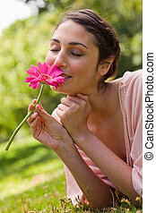 Woman smelling a flower while lying on her front - Woman...