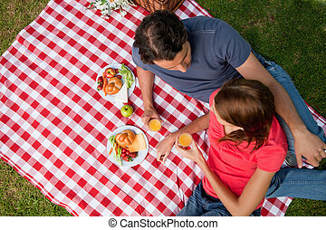 Elevated view of two friends lying on a blanket with a picnic
