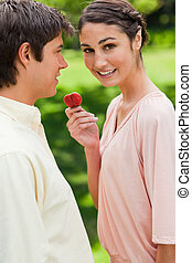 Woman looks towards the side while offering her friend a strawberry in a park