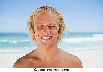 Young smiling man standing on the beach
