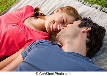 Woman smiling while lying next to her friend on a quilt