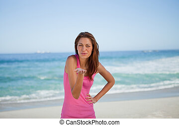 Young woman blowing an air kiss on the beach - Young woman...