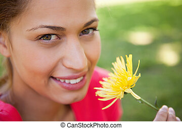 Woman looking towards the camera while holding a yellow...