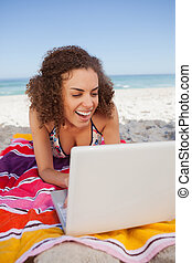 Young attractive woman using a laptop while laughing in front of the ocean