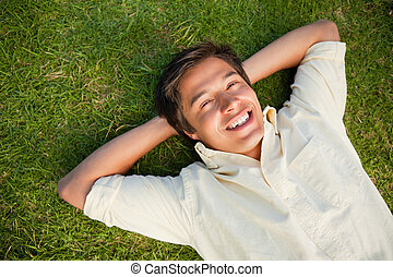 Man smiling as he lies with both hands behind his neck -...