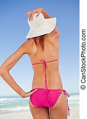 Back view of a teenager in beachwear holding her straw hat in front of the sea