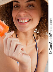 Young woman showing a great smile while holding a Popsicle