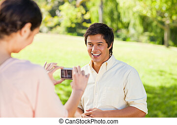 Woman takes a photo of her friend while hes laughing