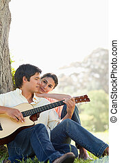 Man looking downwards while playing the guitar as his friend watches him