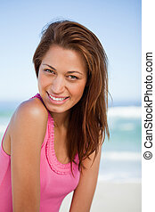 Young smiling woman standing in front of the sea while turning h
