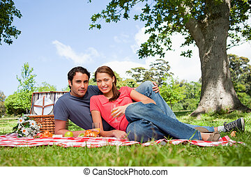 Two friends looking ahead while they hold glasses as they lie on a blanket with a view of the sky and a tree in the background
