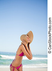Young woman standing on the beach while laughing and holding...