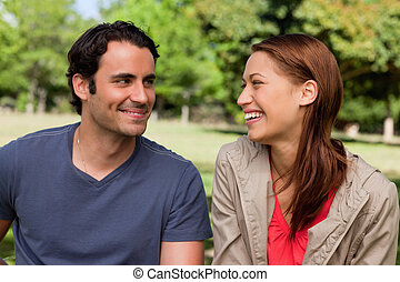 Man is grinning while he watches his friend who is laughing...