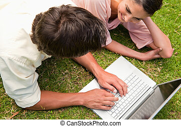 Elevated view of two friends using a laptop together -...
