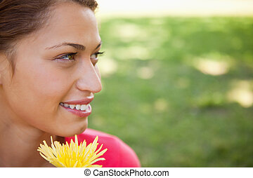 Woman looking towards the side while holding a yellow flower...