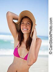 Teenager in beachwear smiling while looking up