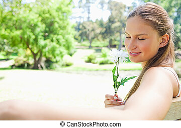 Side view of a woman on a park bench smelling a flower