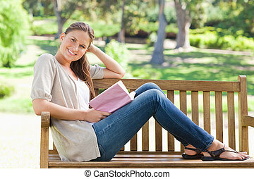Side view of a smiling young woman sitting on a park bench...