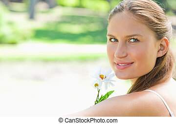 Side view of woman with a flower in the park