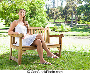 Woman with her legs crossed sitting on a bench - Young woman...